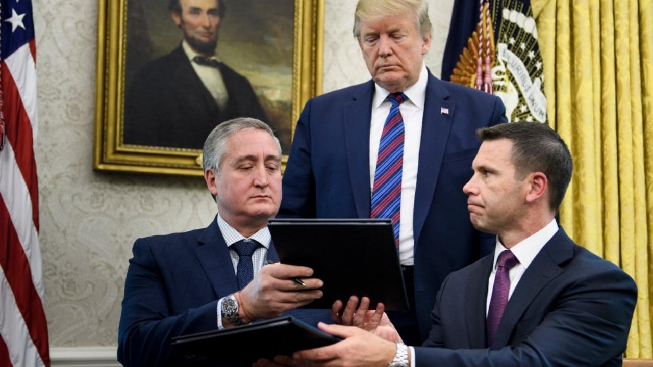 El presidente de los Estados Unidos, Donald Trump, observa cómo el ministro del Interior de Guatemala, Enrique Degenhart, y el secretario interino de Seguridad Nacional de los Estados Unidos, Kevin K. McAleenan intercambian documentos mientras firman un acuerdo de seguridad migratoria.